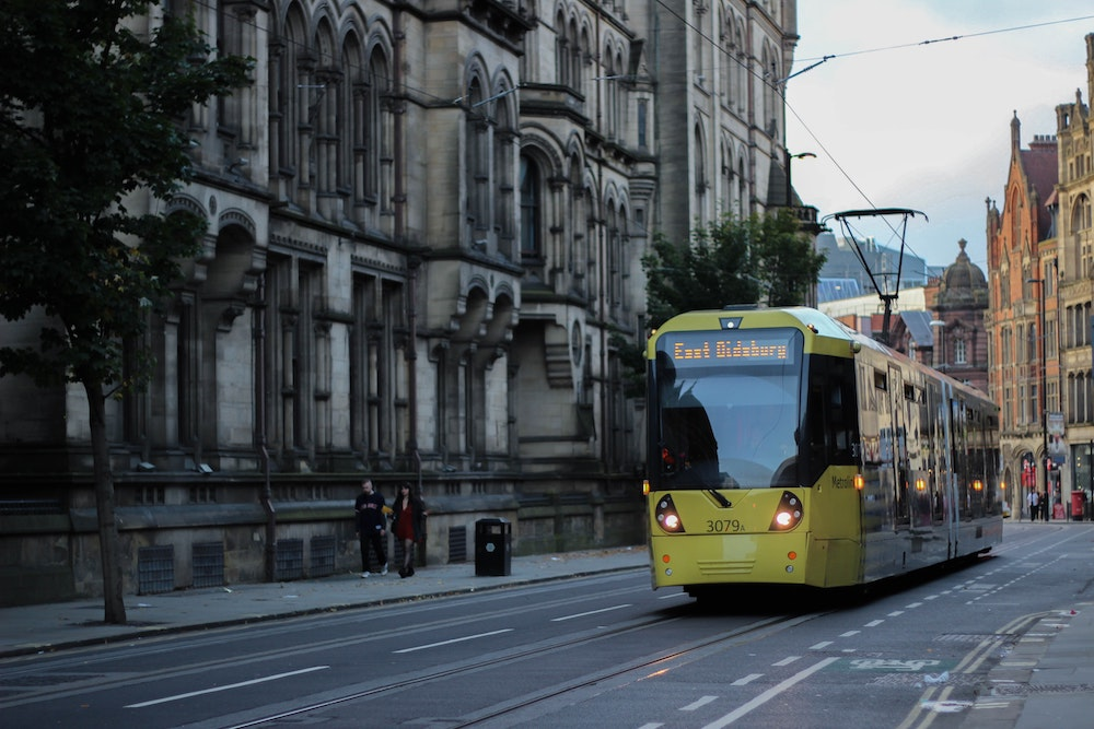 A tram travelling alongside Manchester Town Hall