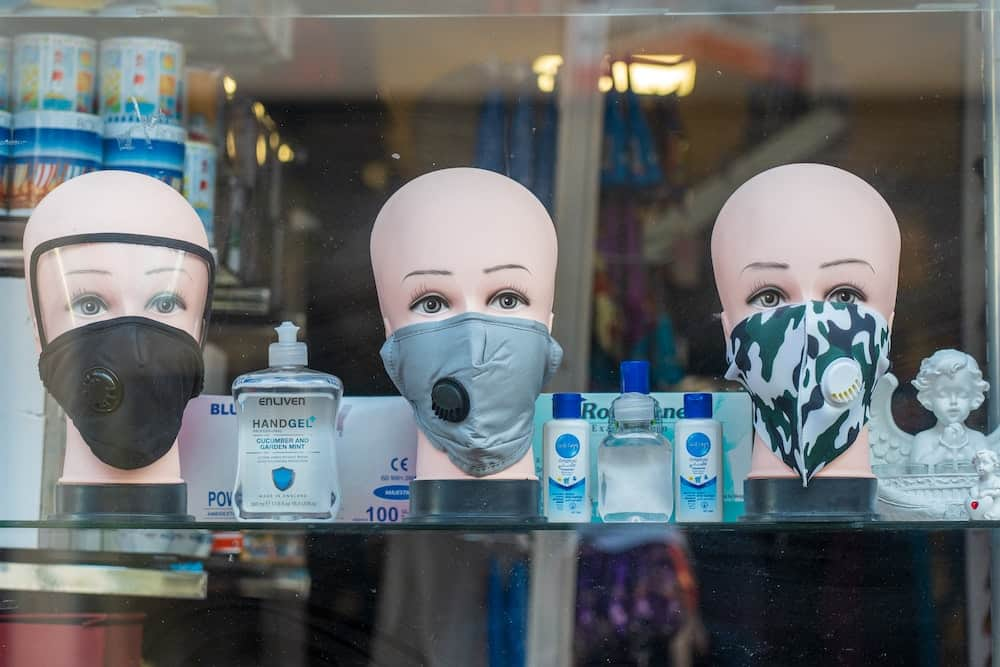 A picture of facemasks on tailor dummy heads in a pharmacy window showing the new normal